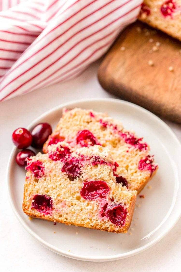 Two slices of cranberry quick bread on a white plate.
