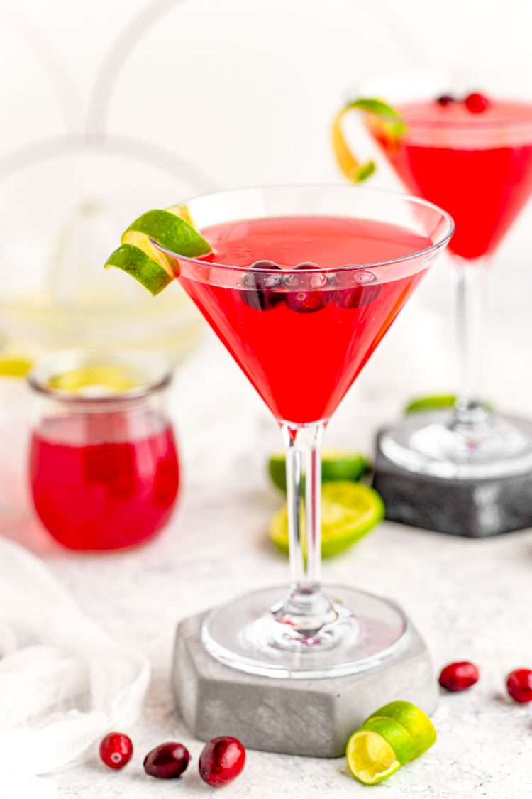 A cosmopolitan martini on a stone coaster garnish with lime rind.