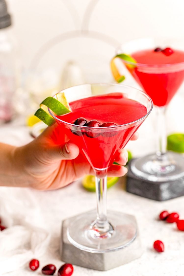 A woman's hand holding a cosmopolitan cocktail.