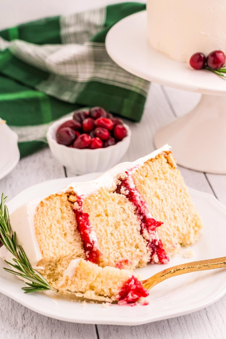 A slice of white cake with cranberry filling on a white plate.