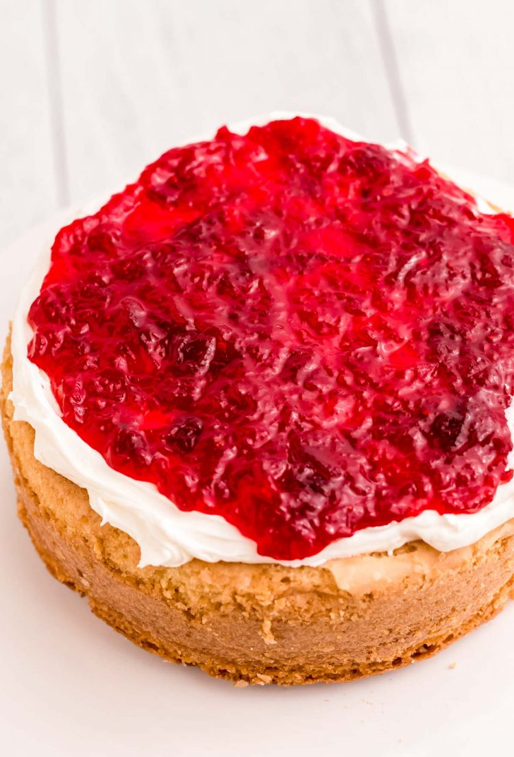A round cake layer being topped with frosting and cranberry compote.