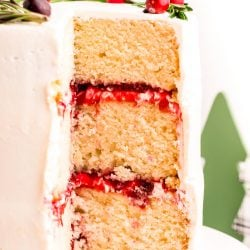 A three-layer cake with cranberry filling and white chocolate frosting that has been cut into to reveal the layers.
