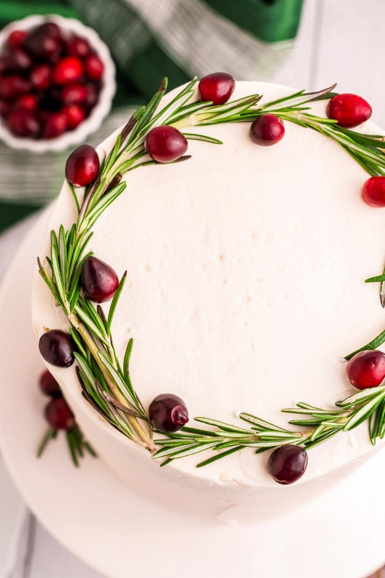 Top down photo of a cake with white frosting and topped with fresh cranberries and rosemary.