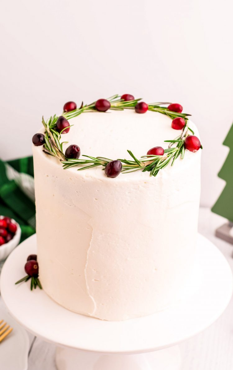 A White frosted layer cake topped with rosemary and cranberries on a white cake stand.