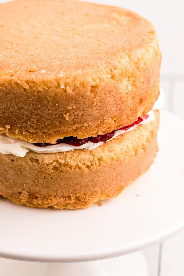 Two layers of cake with white chocolate frosting and cranberry compote between them.