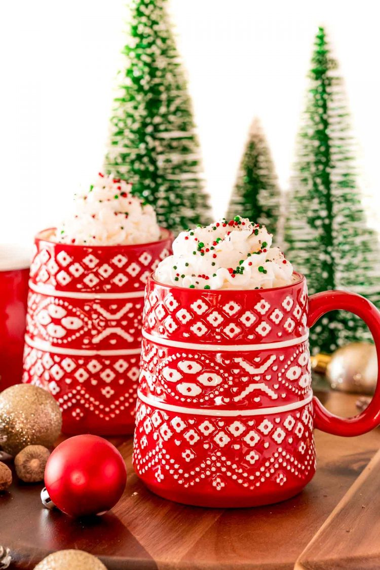 A red mug filled with eggnog hot chocolate and topped with whipped cream and christmas sprinkles.