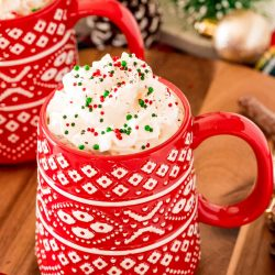 Close up photo of a red Christmas mug filled with hot chocolate and topped with whipped cream and sprinkles.