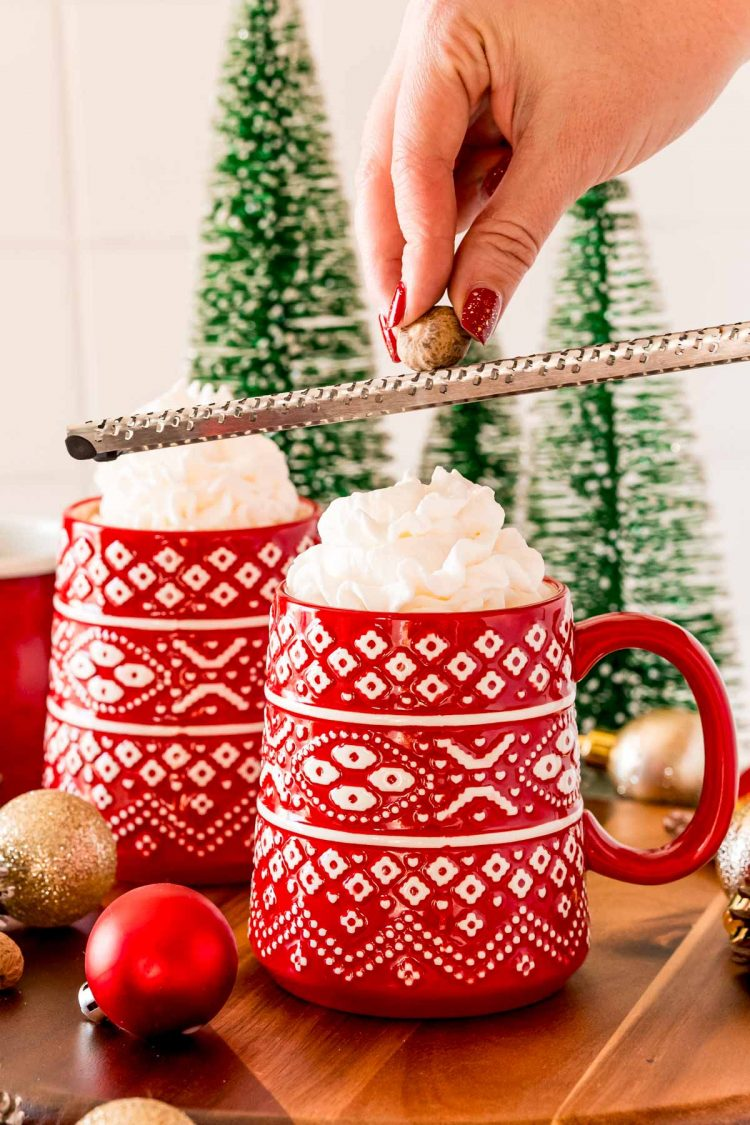 A woman's hand grating a nutmeg over hot chocolate in a red mug.