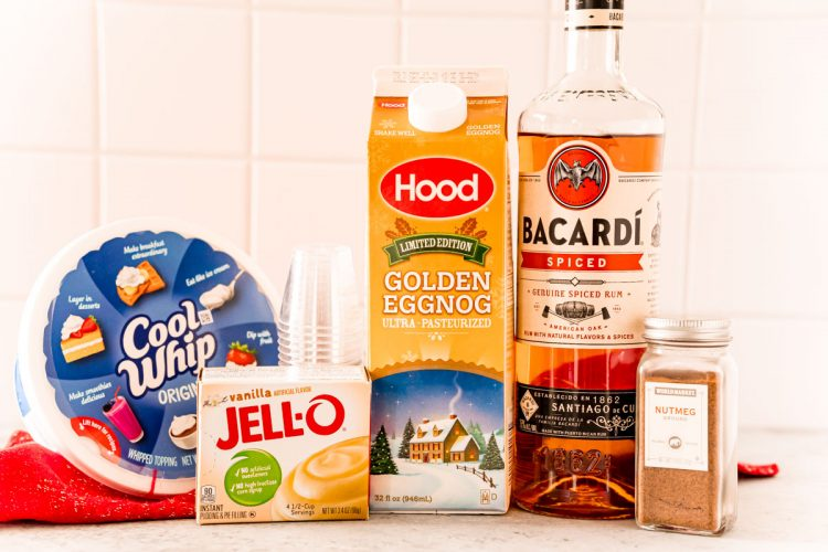 Ingredients to make pudding shots with eggnog and rum on a white table.