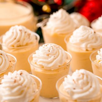 Close up photo of pudding shots topped with whipped cream and nutmeg.
