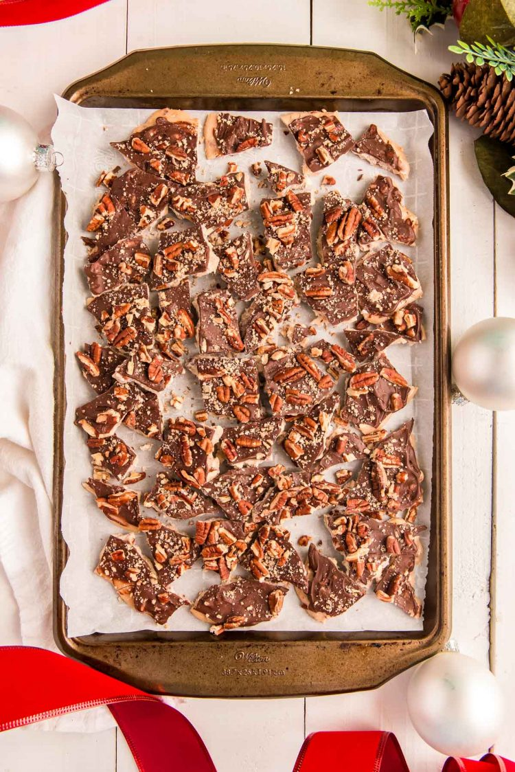 Overhead photo of cracked toffee on a baking sheet with holiday decorations around.
