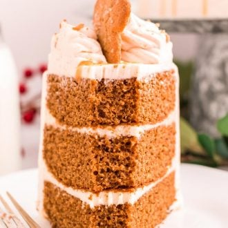 A slice of three layer gingerbread cake with a bite taken out of the front.