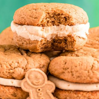 Close up photo of Gingerbread Whoopie pies stacking on eachother on a white plate with a bite taken out of one.