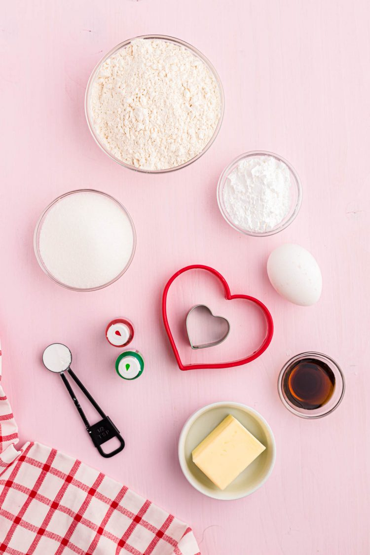 Overhead photo of ingredients to make sugar cookies on a pink surface.