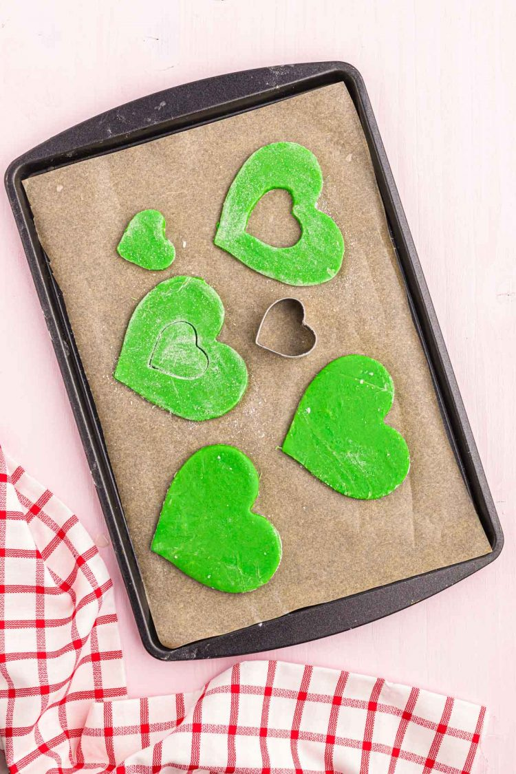 Green heart shaped cookies on a parchment-lined baking sheet.