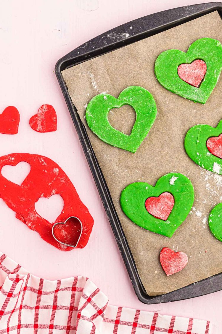 A heart cookie cutter with red and green heart-shaped cookie dough.