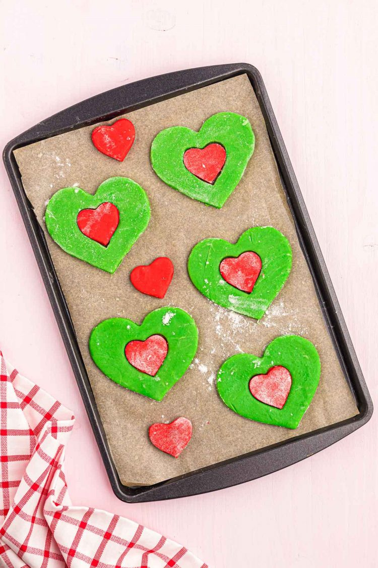 Grinch heart-shaped cookies on a baking sheet ready to bake.