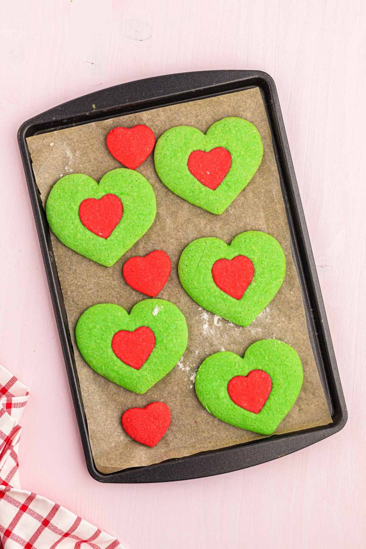 Heart shaped Grinch cookies on a baking sheet.