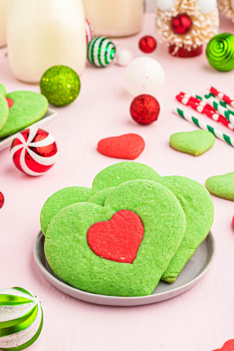 Heart shaped Grinch Cookies inspired by the movie on a plate with holiday decorations in the background.