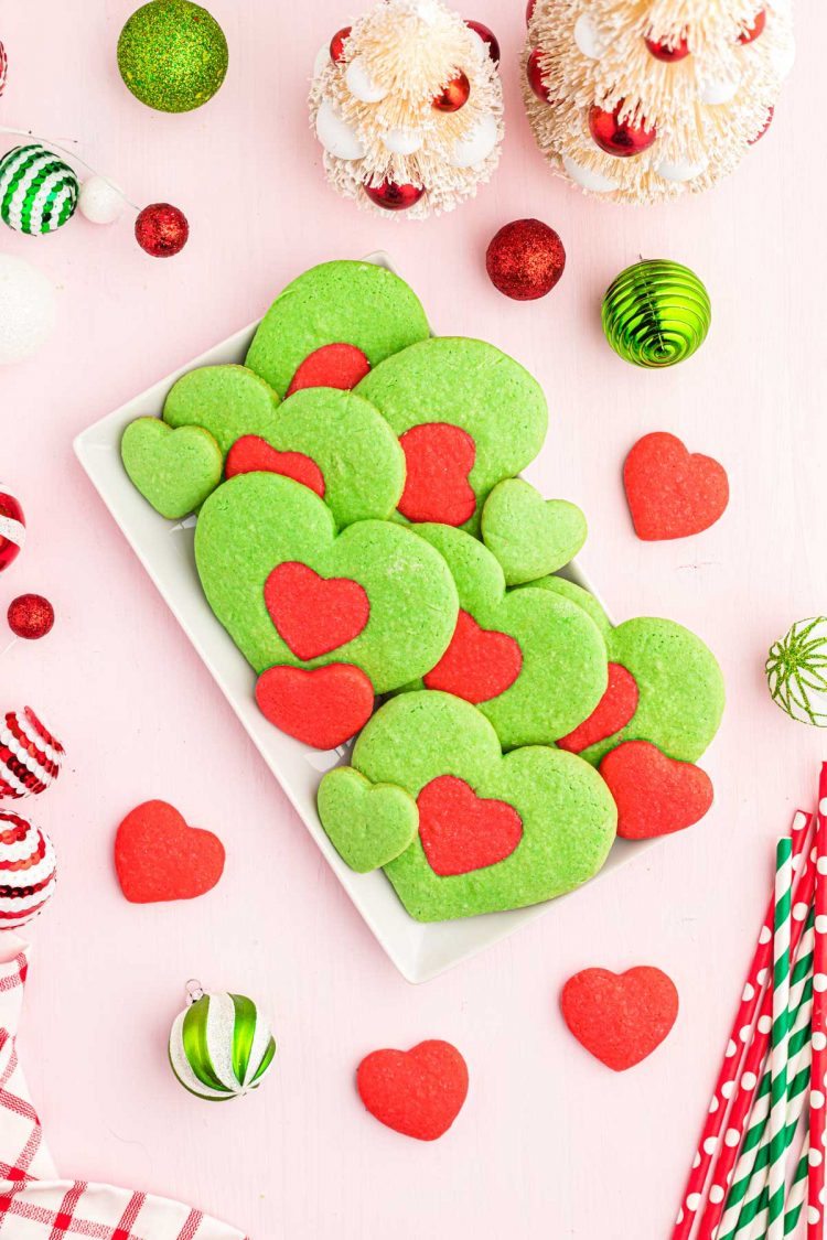 Heart-shaped Grinch cookies on a white plate.