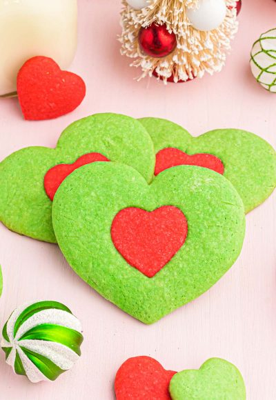 Close up photo of green heart shaped cookies with a red heart in the center inspired by the Grinch.