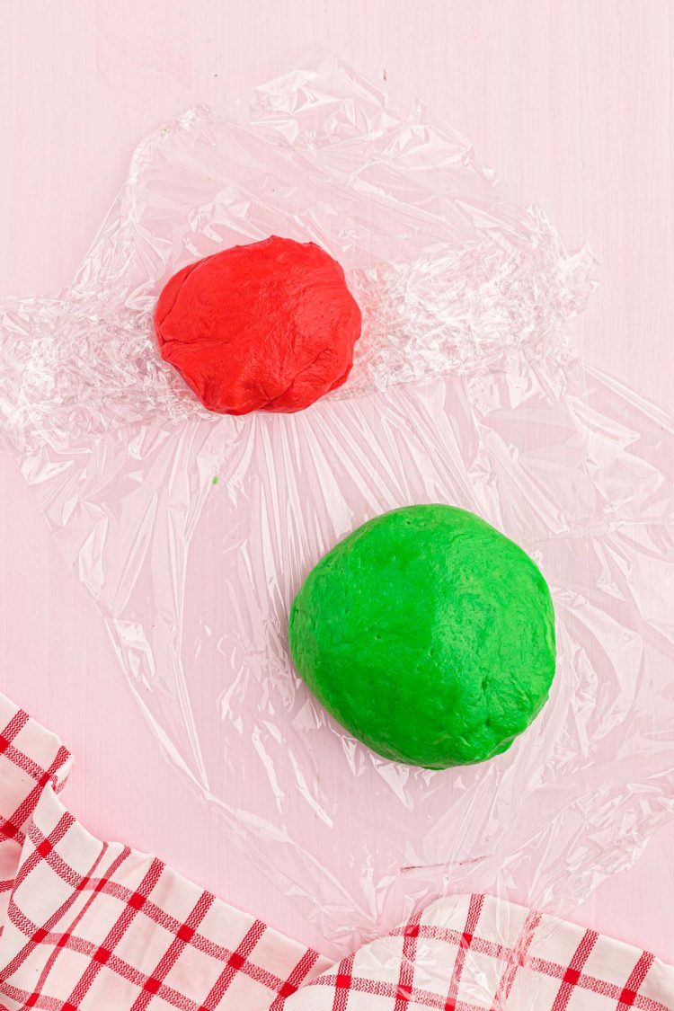 Red and green cookie dough being wrapped in plastic wrap on a pink table.