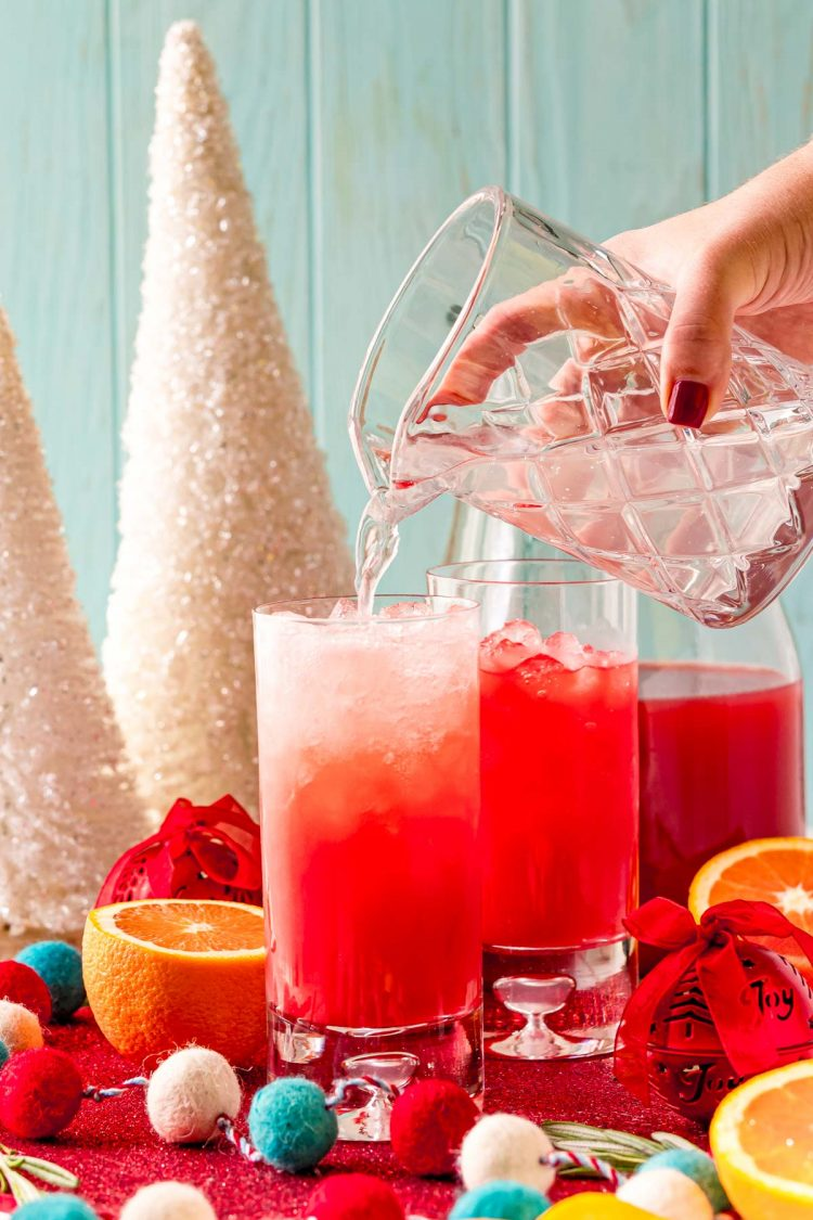 lemon-lime soda being poured into a glass filled with ice and red holiday punch.