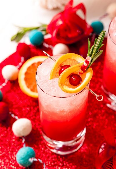 Close up photo of a tall glass filling with a red drink and garnished with oranges and cherries and rosemary.