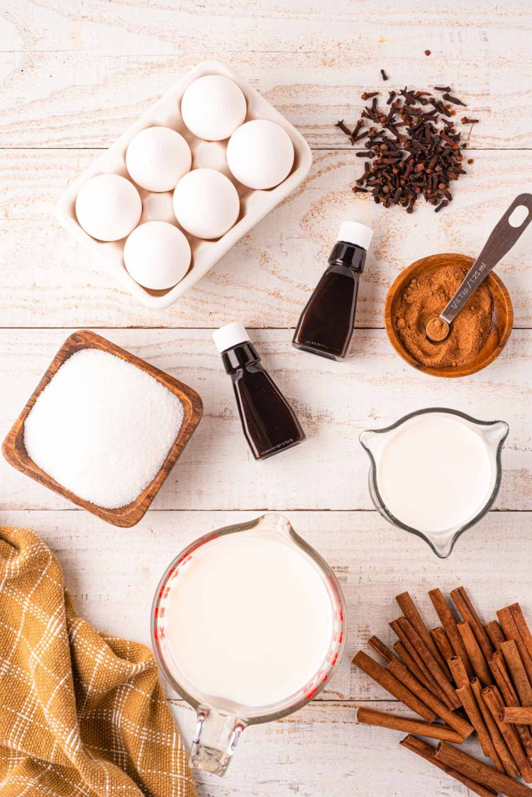 Overhead photo of the ingredients to make homemade eggnog on a light wooden surface.
