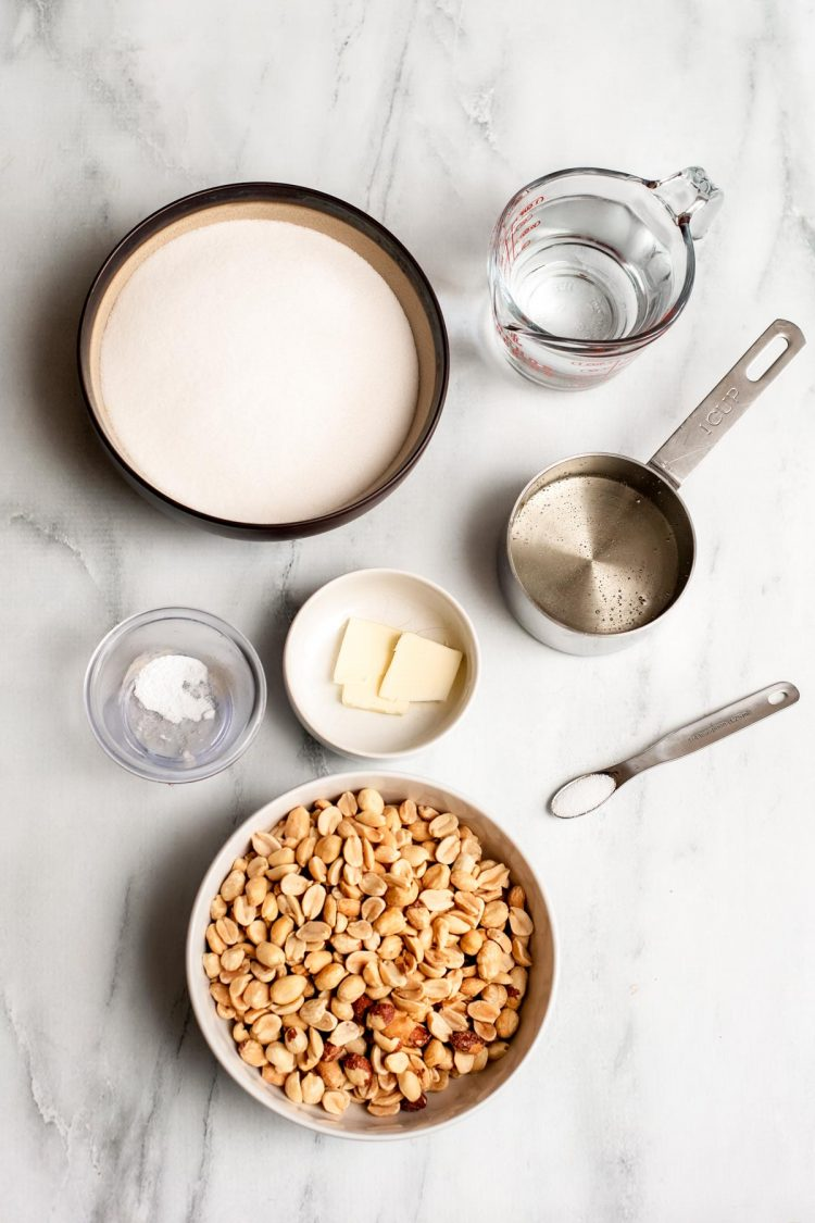 Overhead photo of ingredients to make peanut brittle on a marble surface.