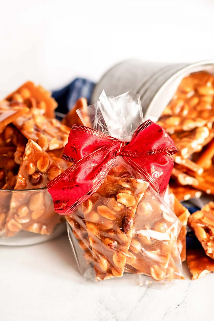Peanut brittle wrapped up in a cello bag with red ribbon.