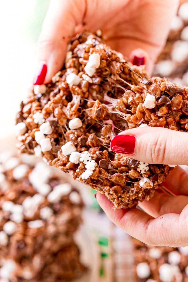A woman's hand tearing apart a chocolate rice krispie treat.