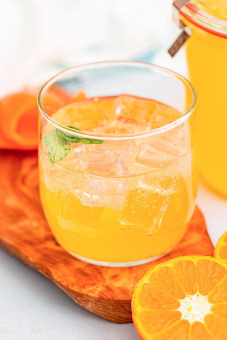 A glass with ice and orange simple syrup.