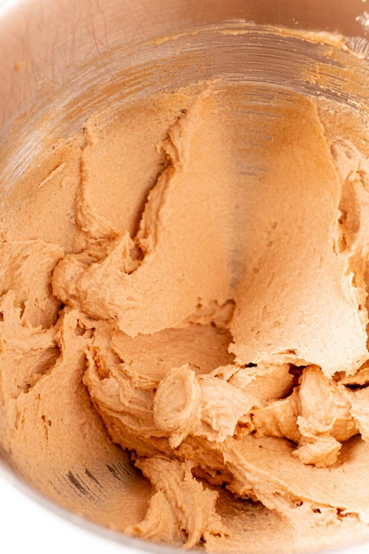 Peanut butter cookie dough in a metal mixing bowl.