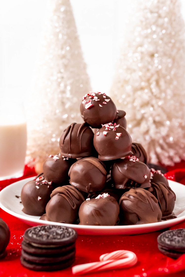 A pile of oreo balls on a white plate with holiday decorations around them.
