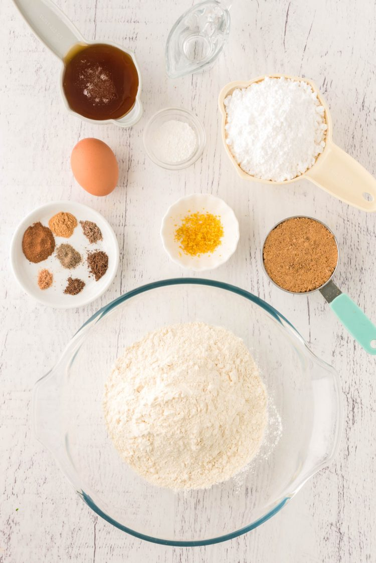 Overhead photo of the ingredients to make pfeffernusse cookies on a white wooden table.