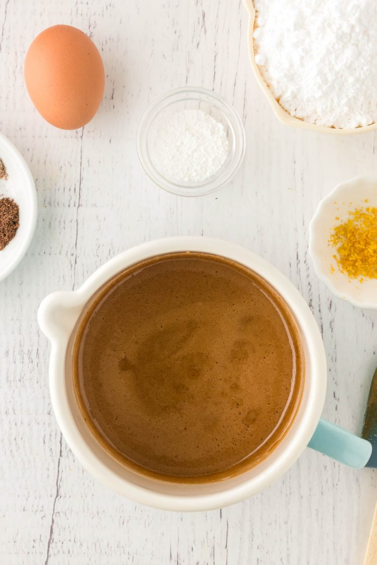 Overhead photo of a pot with melted brown sugar and honey in it with other ingredients around it.
