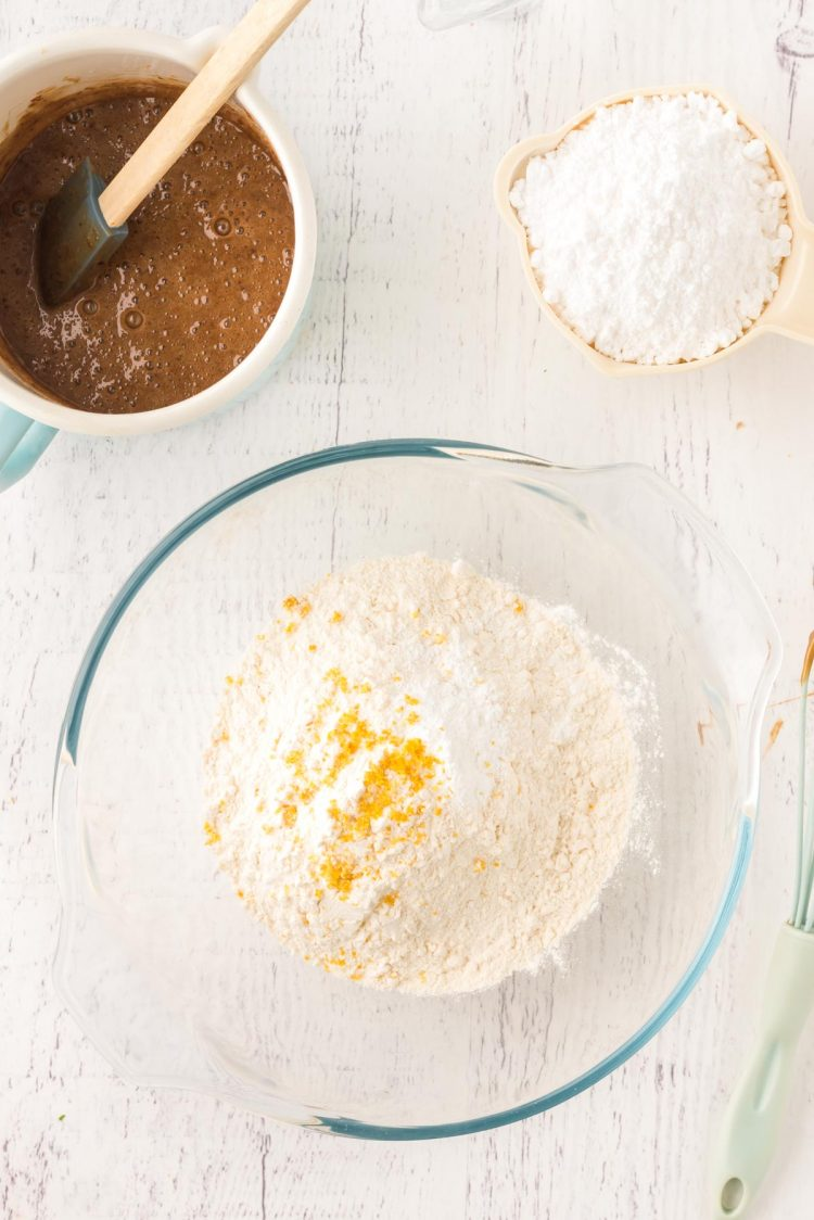 Overhead photo of a glass mixing bowl with flour and lemon zest in it.