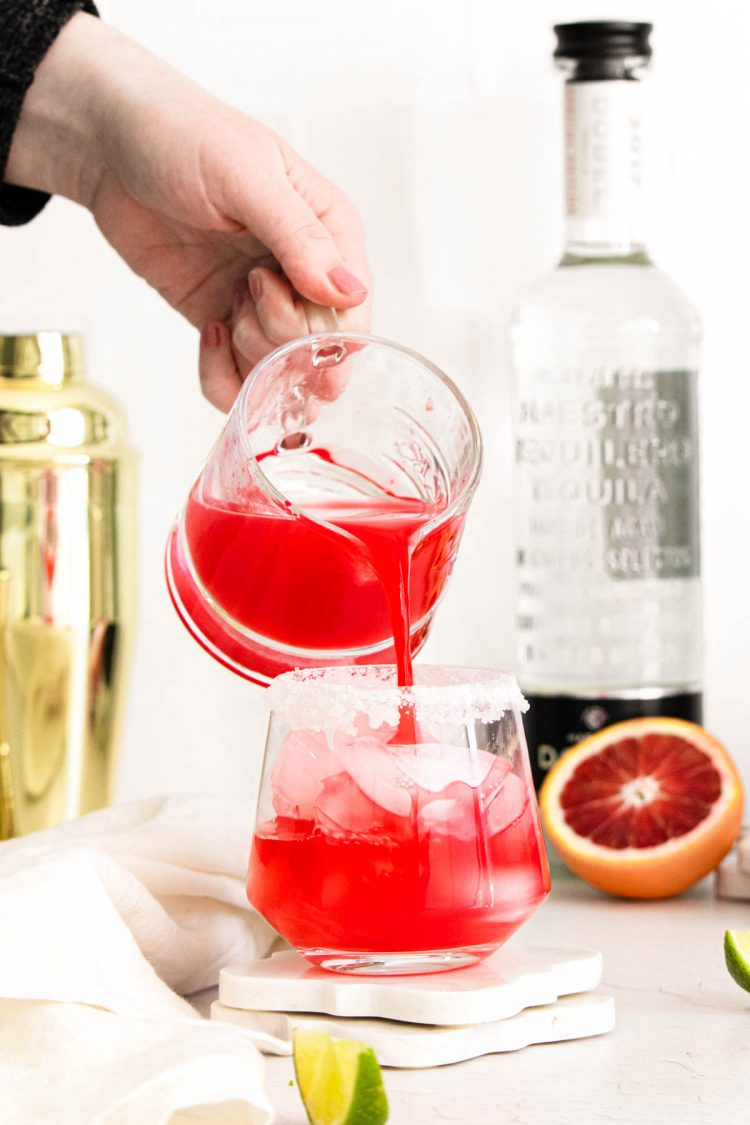 A pitcher pouring a blood orange margarita into a cocktail glass with ice.
