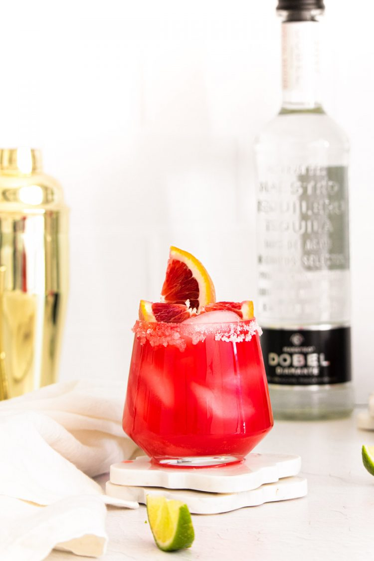 A blood orange margarita with a bottle of vodka and a cocktail shaker in the background.