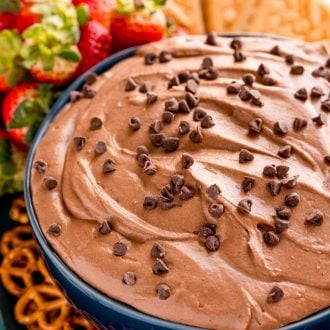 Close up photo of a blue bowl with brownie batter dip in it with pretzels, strawberries and cookies around it.