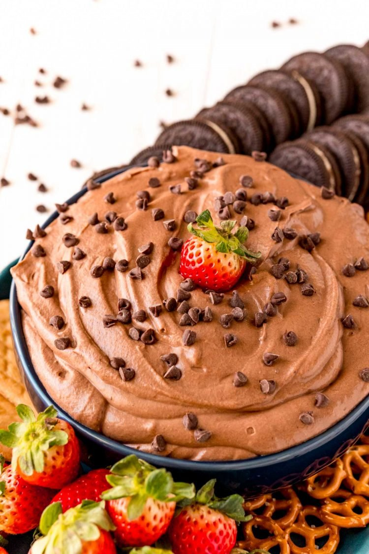 A bowl of brownie batter dip with a strawberry in it.
