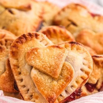 Heart shaped hand pies in a basket with a pink and white striped napkin.