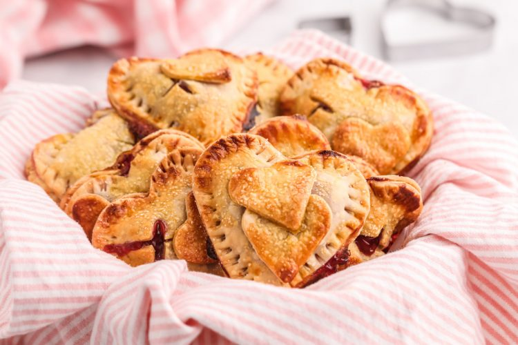 Close up photo of heart shaped hand pies on a white and pink striped napkin.