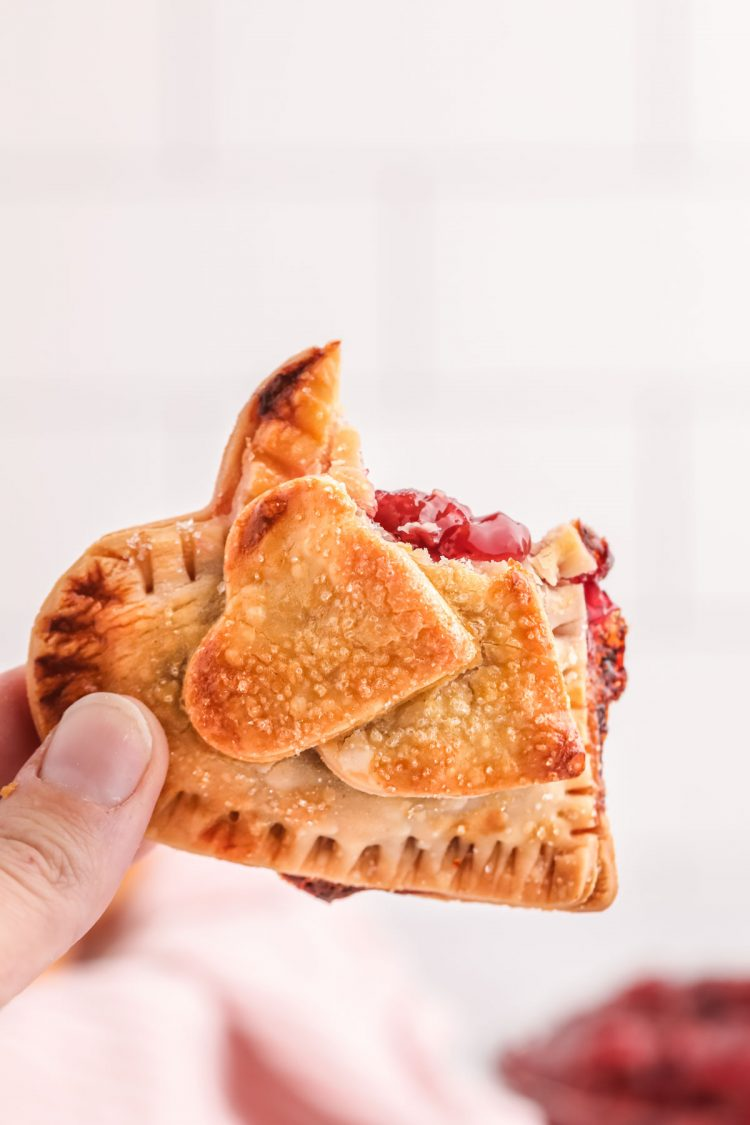 A woman's hand holding a heart shaped cherry hand pie.