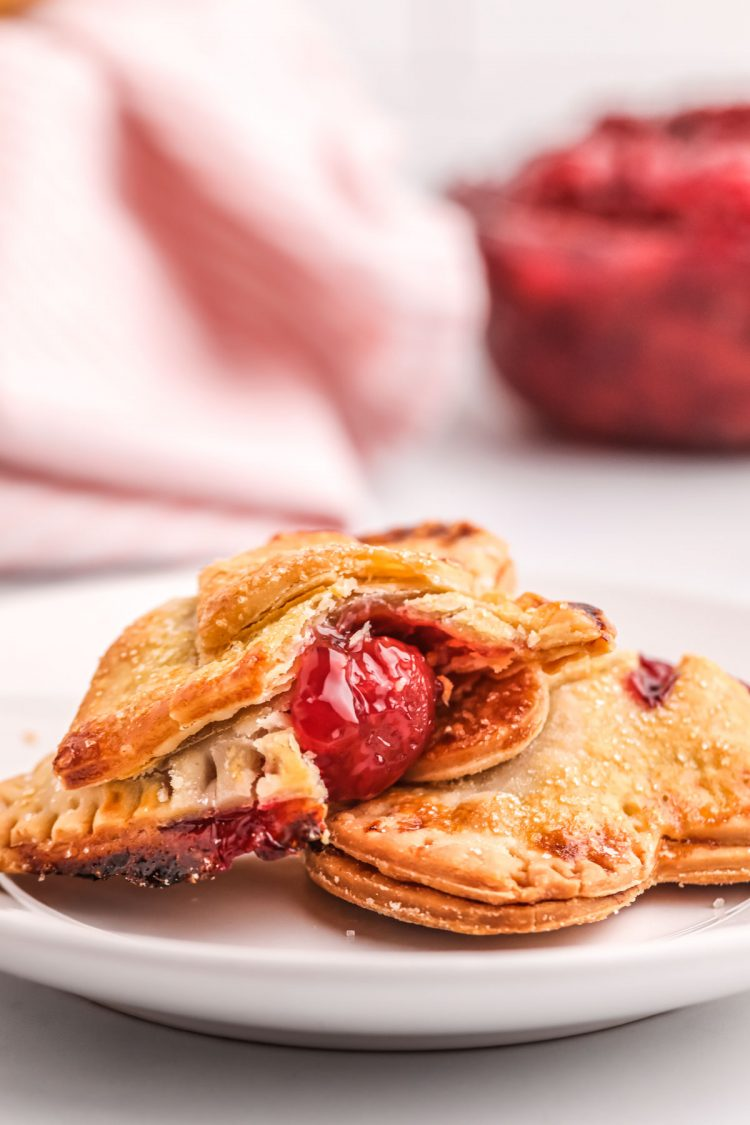 Close up photo of cherry hand pies on a plate, one has a bite taken out of it.