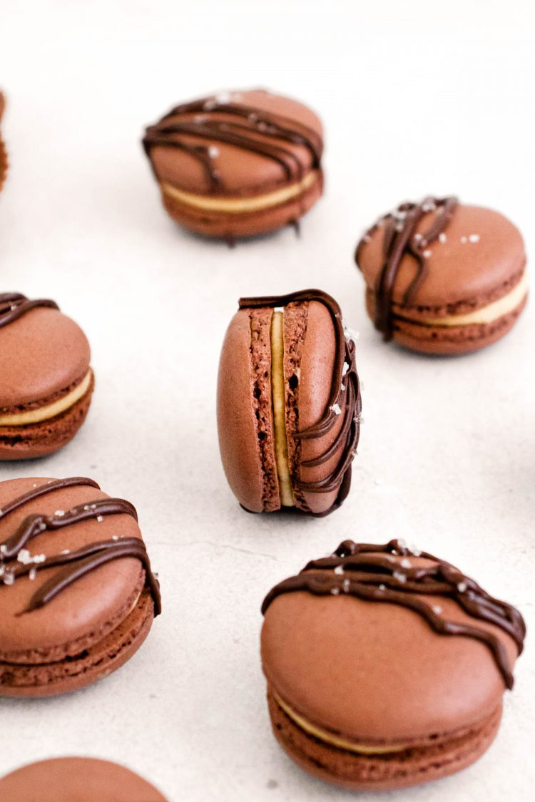 Close up of of peanut butter chocolate macarons on a white counter.