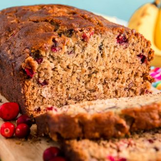 Close up photo of a loaf of cranberry banana bread that had been sliced halfway and is resting on a wooden cutting board.