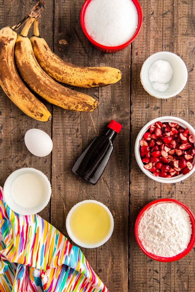 Ingredients to make cranberry banana bread on a wooden table.