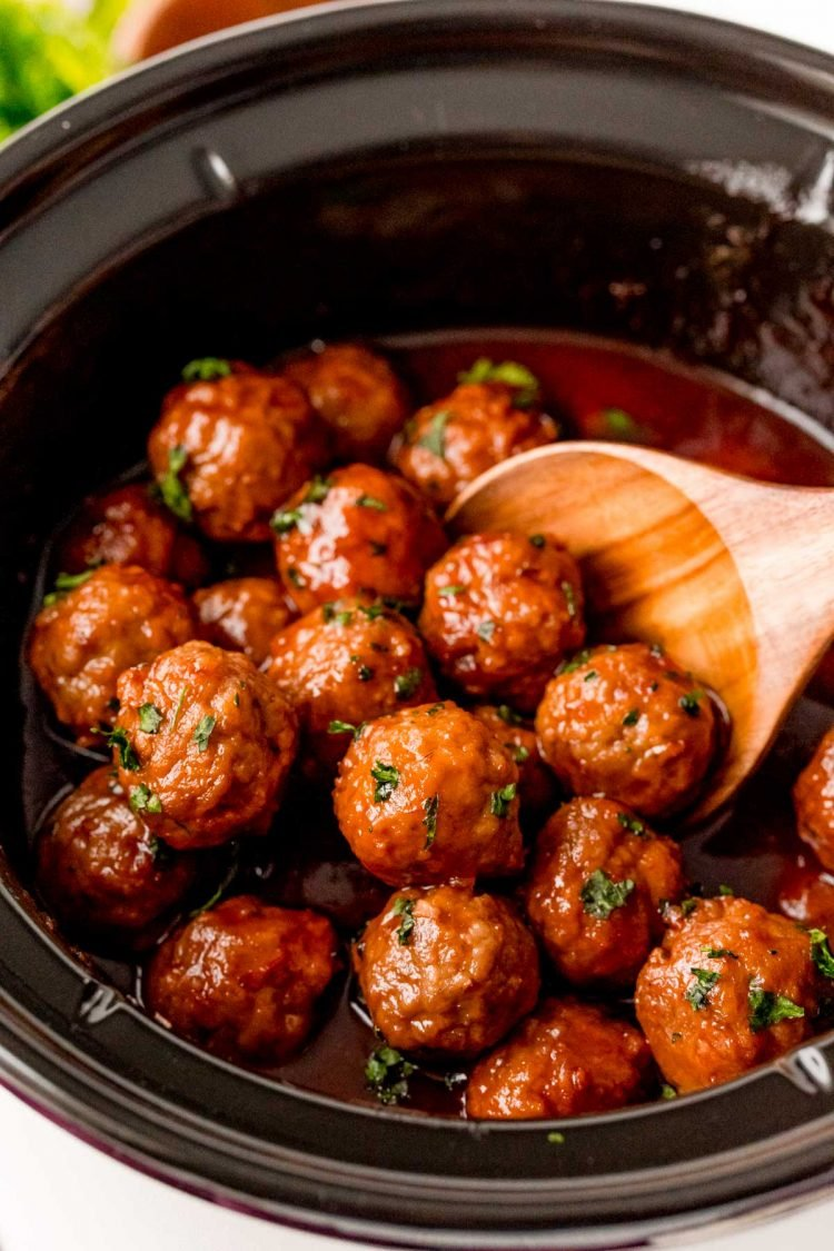 A wooden spoon in a crockpot filled with meatballs.